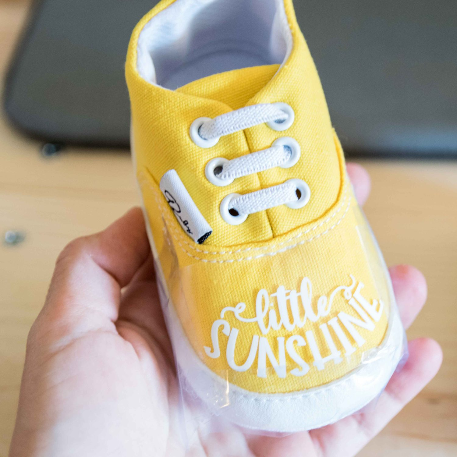 Taping design to baby shoe with heat transfer tape