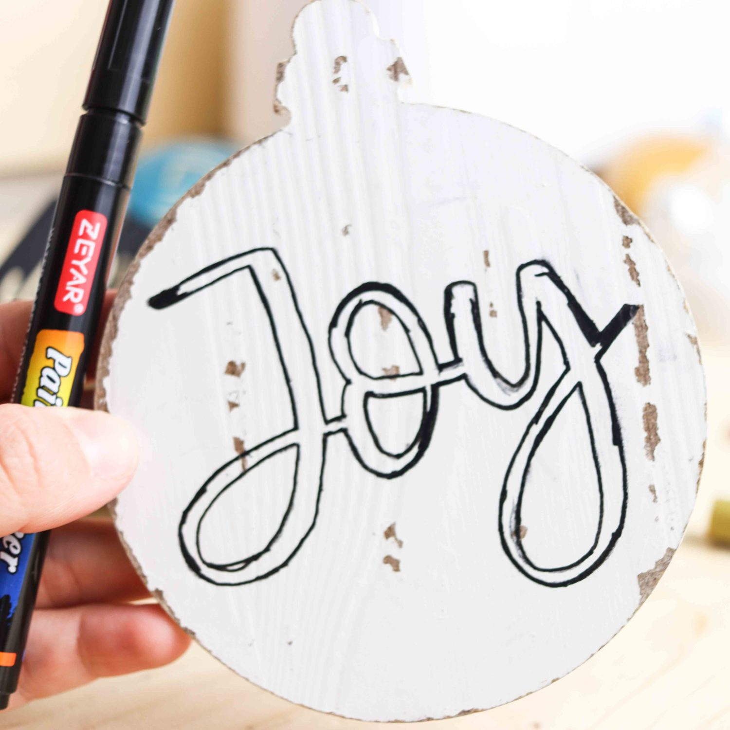 Outlining design on wooden Christmas Ornament